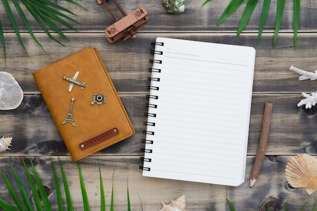 Flat lay blank notepad with passport book, shells and palm leaves.