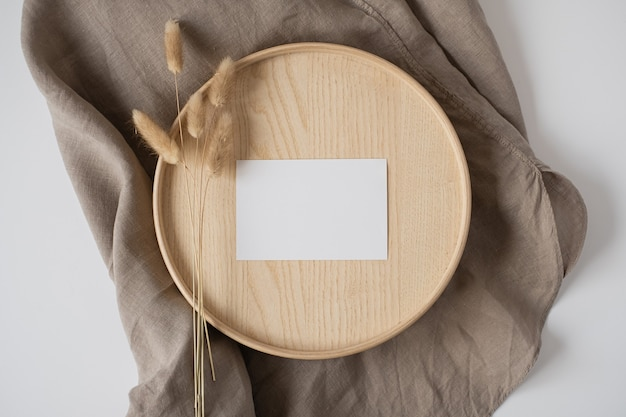 Flat lay of blank paper business card on neutral beige blanket