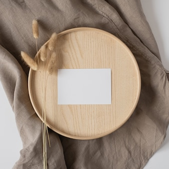 Flat lay of blank paper business card with bunny tail on wooden tray on neutral beige blanket