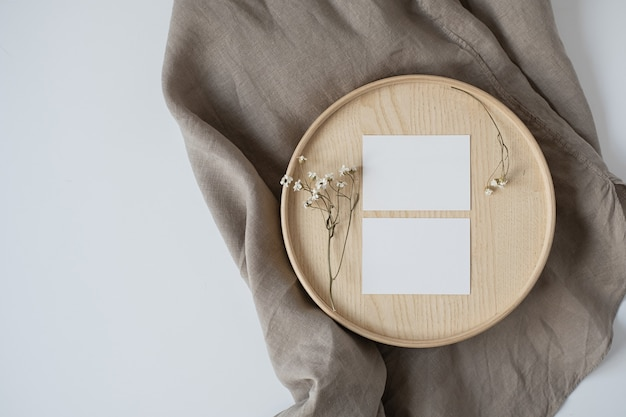 Flat lay of blank paper business cards with flowers on wooden tray on neutral beige blanket