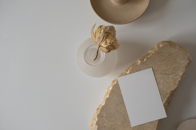 Flat lay of blank paper sheet card with flower, marble stone
