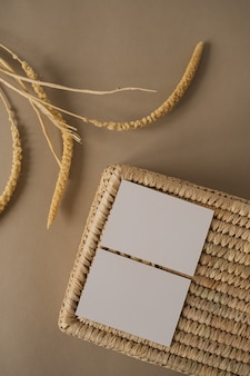 Flat lay of blank paper sheet cards with rattan casket on neutral beige
