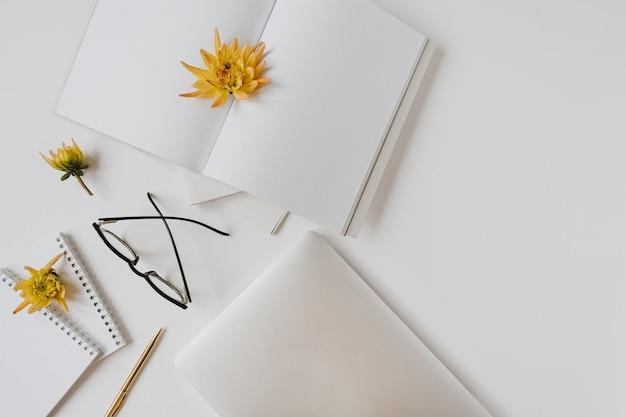 白地に白紙、ノート、メガネ、ラップトップ、花のつぼみを平らに置きます。ホームオフィスデスクワークスペース。フラットレイ、上面図。