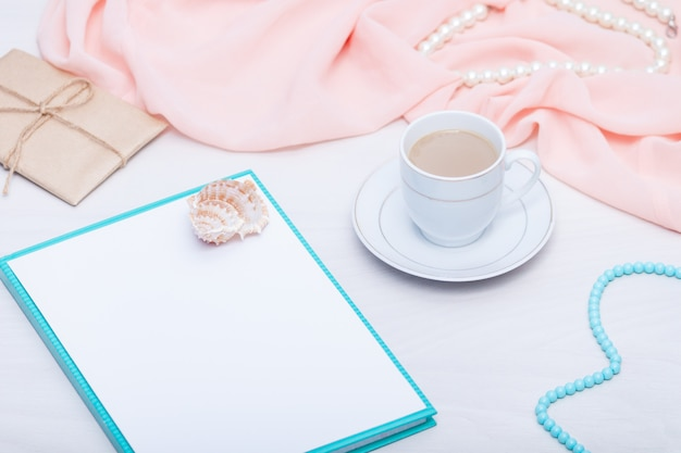 Flat lay of blank paper sheet with coffee cup and jewellery