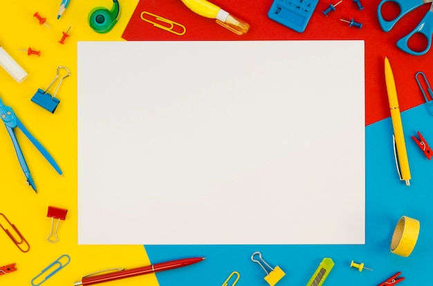 Flat lay of blank paper with office supplies background