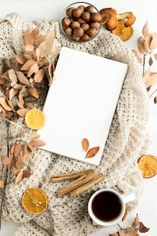 Flat lay of blank placard with autumn leaves and cinnamon sticks