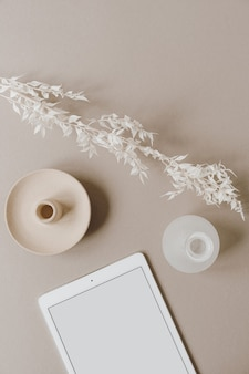 Flat lay of blank screen tablet pad, white floral branch, decorations on neutral pastel beige. home office desk workspace. flat lay, top view.