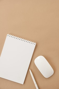 Flat lay of blank sheet spiral notebook on pastel beige. minimalist home office desk workspace. business, work template. flat lay, top view