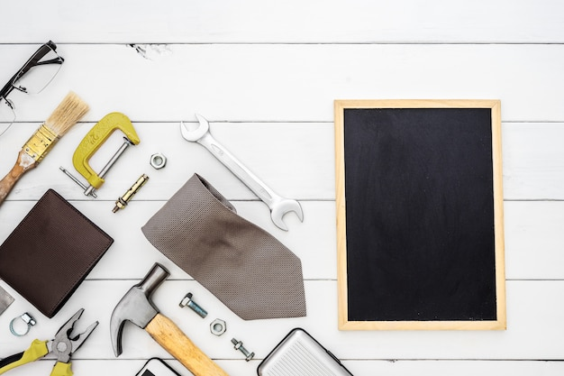 Flat lay of blank space blackboard with construction blue collar handy tools and men's accessories over wooden background.