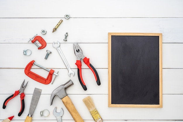 Flat lay of blank space blackboard with construction handy tools over wooden background.