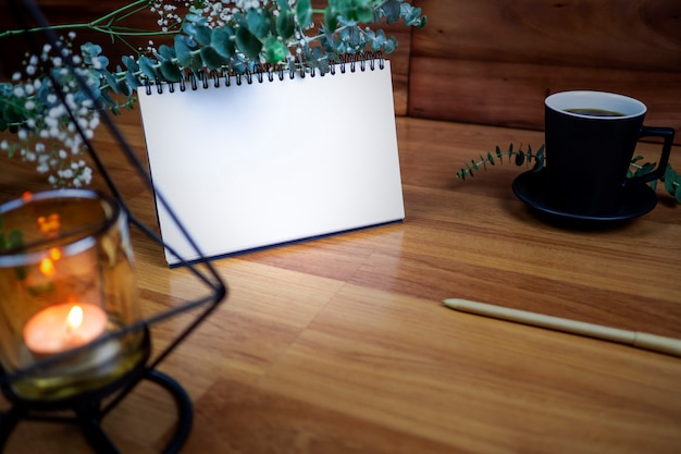 Flat lay of blank white notebook with cup coffee on wooden table.