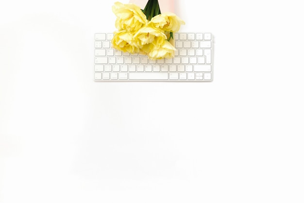 Flat lay blogger or freelancer workspace. an office white desk with a keyboard and a bunch of yellow spring tulips on it. copy space. minimalistic trend background