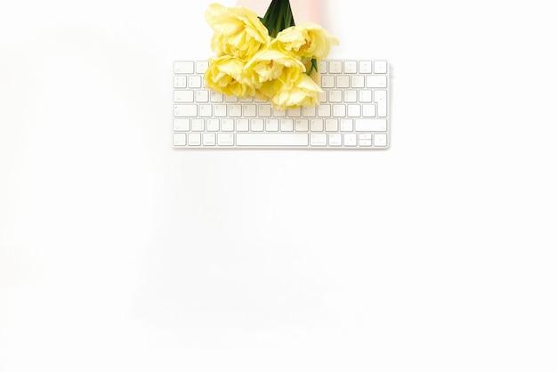 Плоское рабочее место блоггера или фрилансера. стол офисный белый с клавиатурой и букет желтых весенних тюльпанов на нем. копировать пространство минималистичный тренд фон