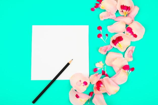 紙のカード、色の背景に明るいピンクの花びらを持つフラットレイアウトのブロガーまたはフリーランサーのワークスペース