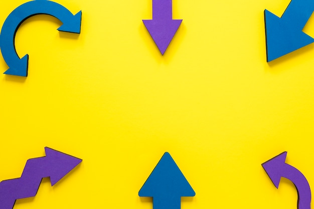 Плоские лежали синие и фиолетовые стрелки кадр на желтом фоне