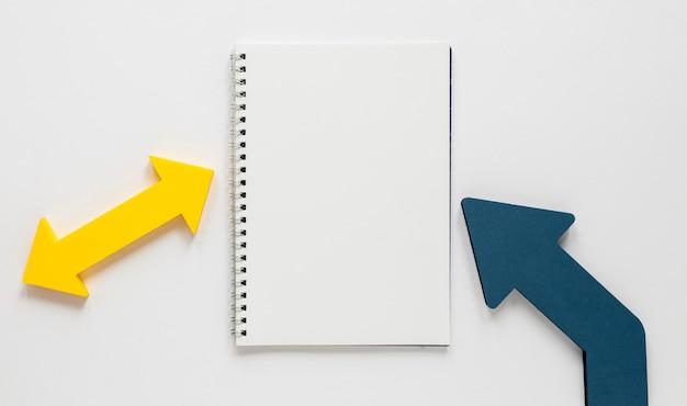 フラット横たわっていた青と黄色の矢印とノートブックモックアップ