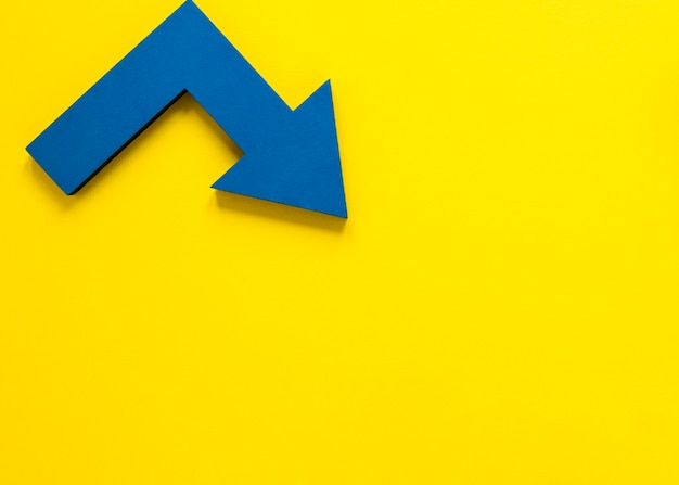 Freccia blu di disposizione piana su fondo giallo con copia-spazio