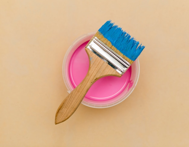 Flat lay of blue brush and pink paint bucket