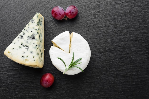Flat lay blue cheese camembert and grapes with copy space