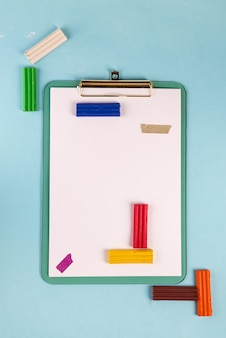 Flat lay blue clipboard with plasticine on a blue and tetris game