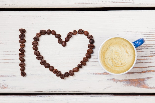 Flat lay blue cup of coffee and beans arranged in a heart. i love coffee. white wood surface.