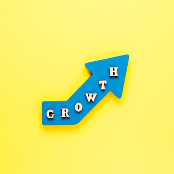 Flat lay blue growth arrow on yellow background