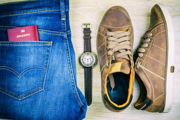Flat lay. blue jeans, shoes, passport and wristwatch