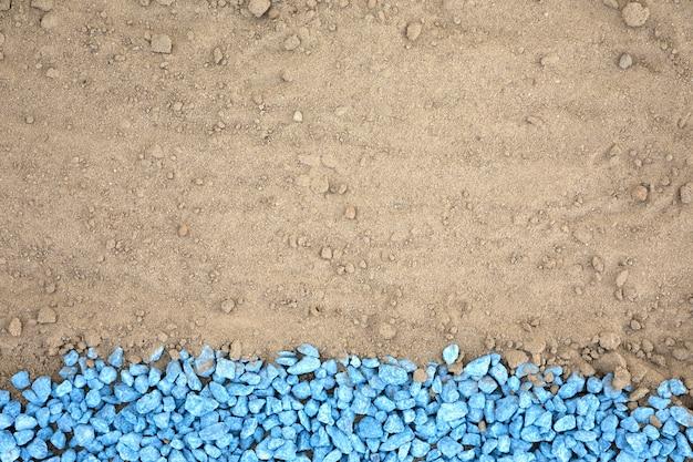 Flat lay blue pebbles on sand