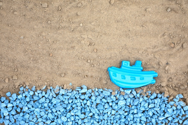 Flat lay blue pebbles with boat on sand