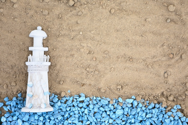 Flat lay blue pebbles with lighthouse on sand