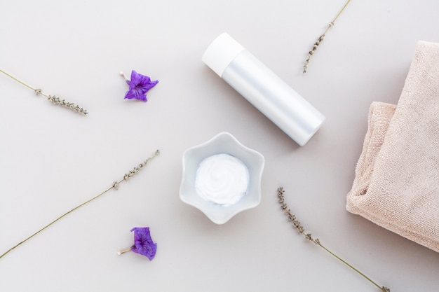 Flat lay of body butter and bottle on plain background