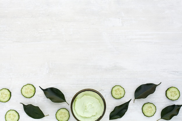 Flat lay of body butter and cucumber on wooden table with copy space