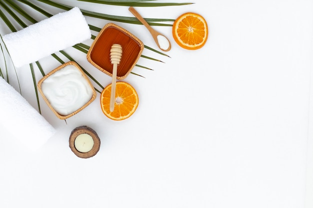 Flat lay of body butter honey and orange on white background