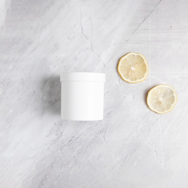 Flat lay body butter and lemon slices on marble background