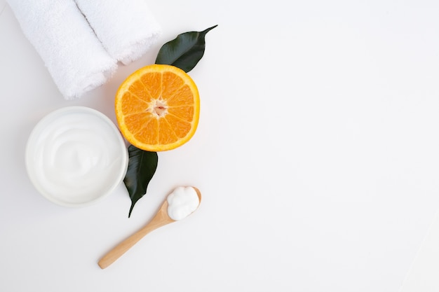 Flat lay of body butter and orange on plain background