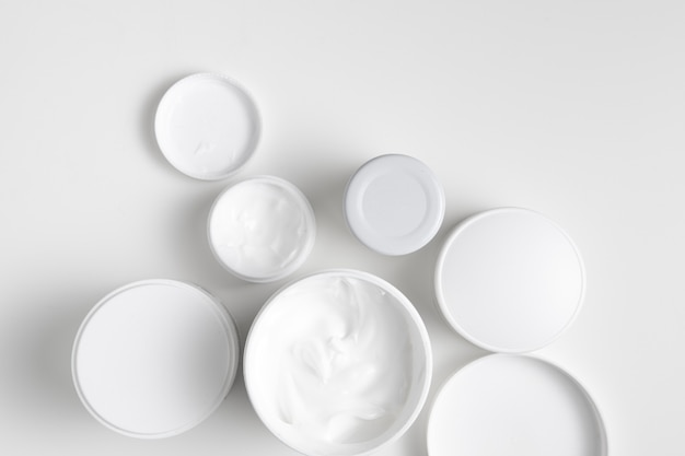 Flat lay body care containers on plain background