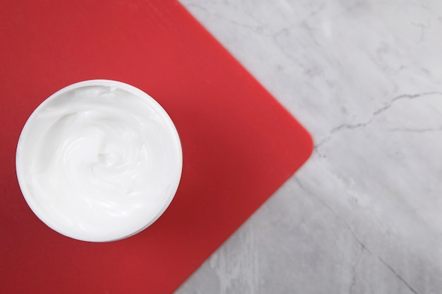 Flat lay body cream on red board