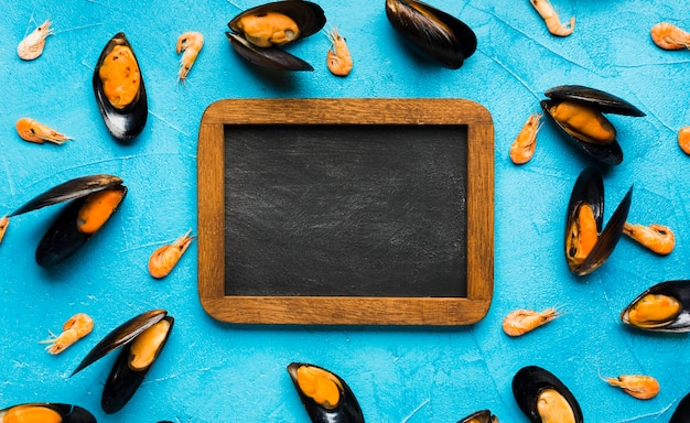 Flat-lay boiled mussels with blackboard