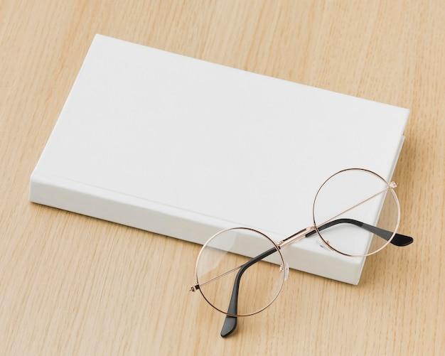 ガラスとテーブルの上のフラット横たわっていた本