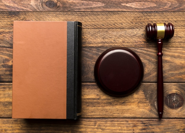 Flat lay book with judge gavel and stand