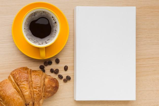 コーヒーとクロワッサンのテーブルの上の平らな本を置く