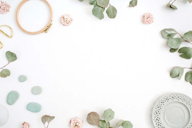 Flat lay border frame with eucalyptus branches, plate on white