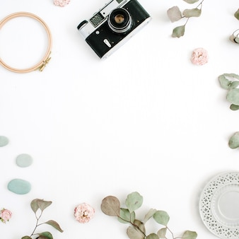 Flat lay border frame with retro camera, eucalyptus branches, plate on white