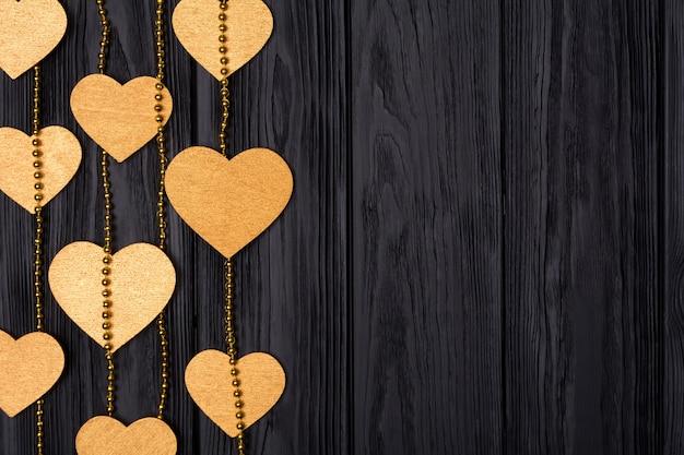 金色のハートとビーズのフラットレイボーダー。黒の木製の背景にお祝いの装飾。上からの眺め。