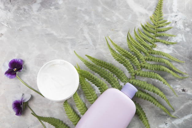 Flat lay of bottle and body cream on marble background