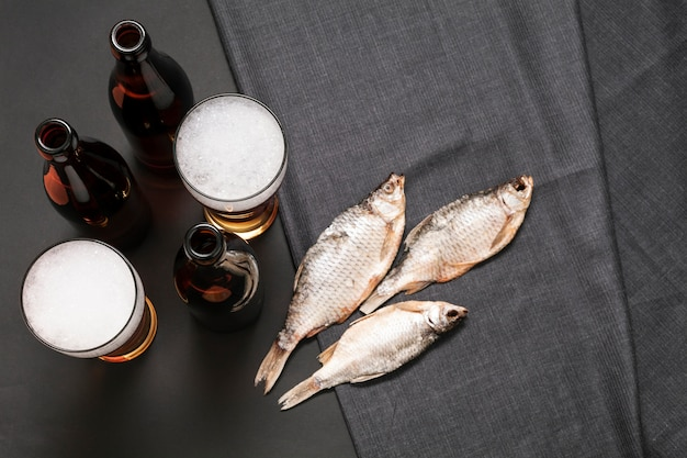 Flat lay bottles and glasses of beer with fish