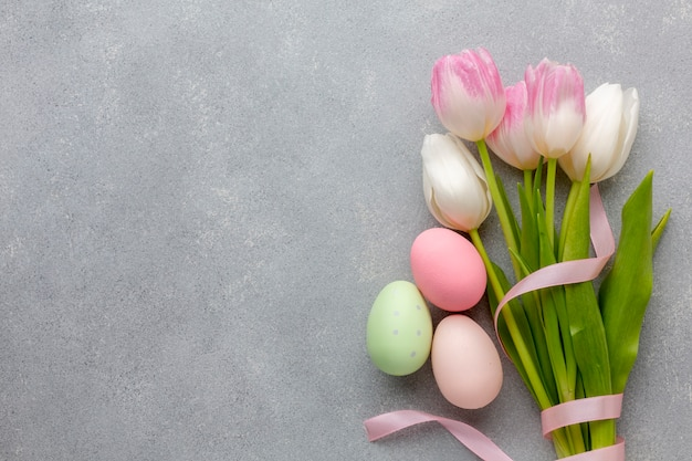 Flat lay of bouquet of tulips with colorful easter eggs