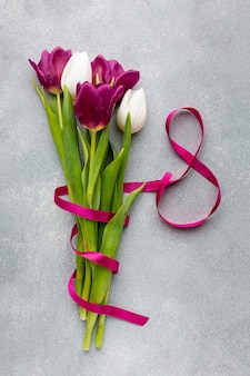 Flat lay bouquet of tulips with pink ribbon