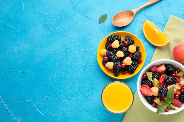 Flat-lay bowl of fresh berries and fruits with copyspace