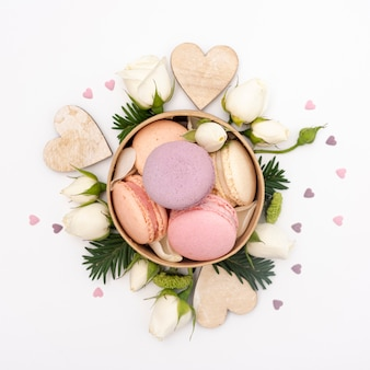 Flat lay of bowl with macarons and roses